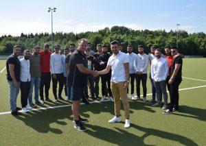 """Trainer Frank Sippli und Vorsitzender Hakan Aslantas im """"Handshake"""" und das Team lächelt dazu. Foto: TME"""